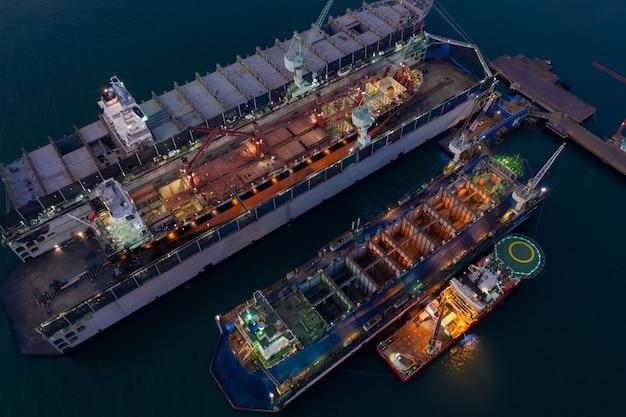 Widok z lotu ptaka kontenerowiec i olej w stoczni do naprawy w nocy. można użyć do koncepcji wysyłki lub transportu.