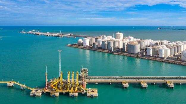 Widok z lotu ptaka ładowniczego ramienia rafineria ropy i gazu przy portem handlowym, cysternowy terminal z udziałami zbiornik na olej i petrochemiczny zbiornik w porcie, przemysłowy zbiornikowy widok z lotu ptaka.