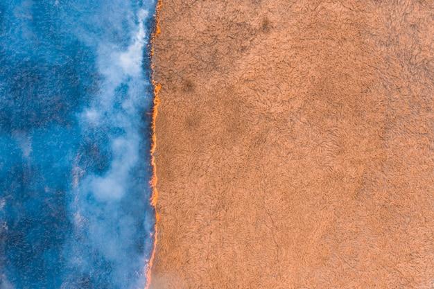 Widok z lotu ptaka łąka z suchą płonącą trawą.
