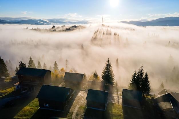 Widok z lotu ptaka małej wioski domów na szczycie wzgórza w jesiennych mglistych górach o wschodzie słońca.