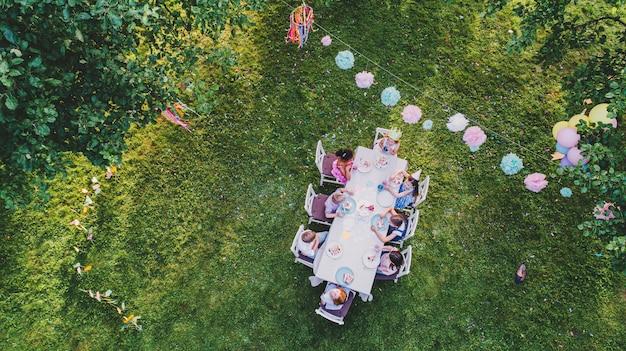 Widok z lotu ptaka małych dzieci siedzących przy stole na letnie przyjęcie w ogrodzie, koncepcja obchodów urodzin.