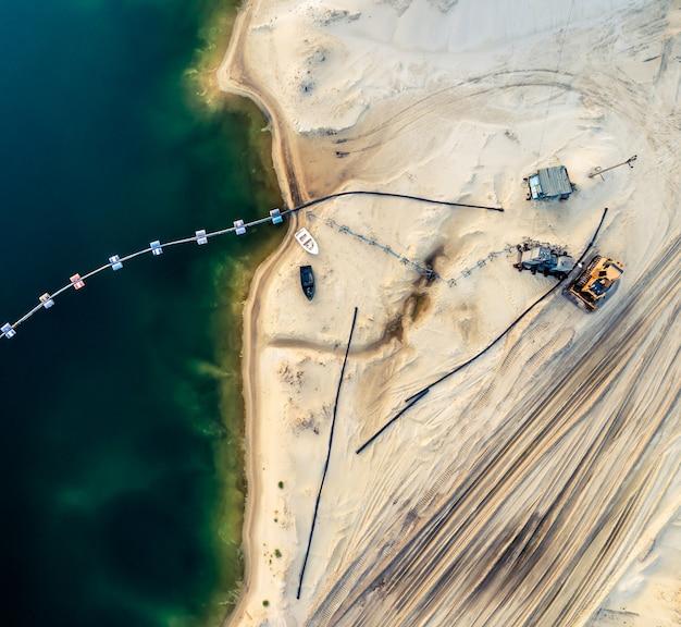 Widok z lotu ptaka maszyn i urządzeń kopalnianych w pobliżu ciemnoniebieskiego jeziora