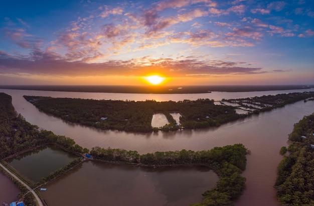 Widok z lotu ptaka mekong delty rzeki region, ben tre, południowy wietnam. kanały wodne i tropikalne wyspy fluwialne dramatyczne niebo o zachodzie słońca.