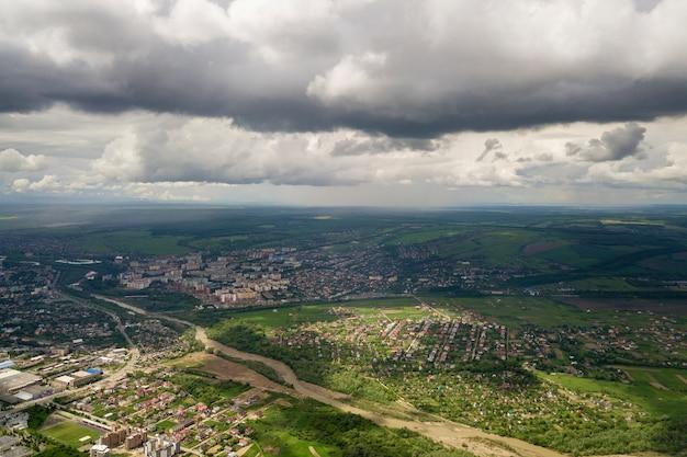 Widok z lotu ptaka miasta lub wioski z rzędami budynków i ulic między zielonymi polami w lecie.