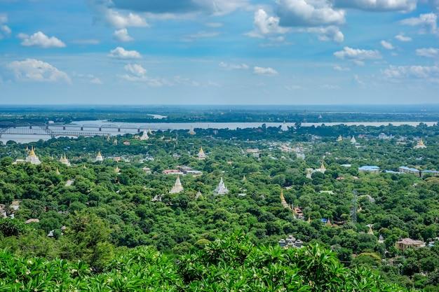 Widok z lotu ptaka miasta mandalay ze świątyniami, złotą pagodą, rzeką irrawaddy i mostami ze wzgórza sagaing. punkt orientacyjny i popularny wśród turystów atrakcji w birmie