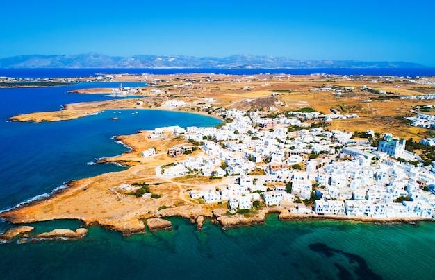 Widok z lotu ptaka miasta naoussa z typowymi białymi domami nad morzem i niskimi górami na horyzoncie, wyspa paros, grecja