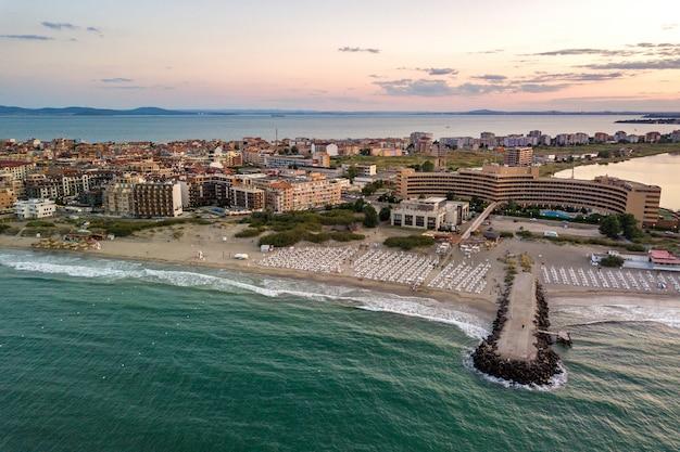 Widok z lotu ptaka miasta pomorie, który znajduje się na brzegu morza czarnego. widok z góry na piaszczyste plaże z wieloma budynkami hotelowymi i infrastrukturą turystyczną.