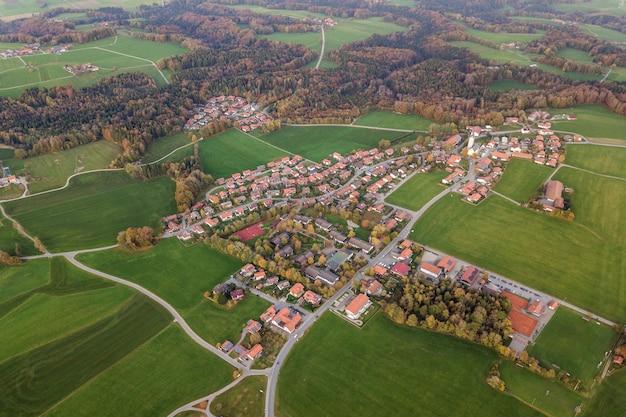 Widok z lotu ptaka miasteczko z czerwonymi kafelkowymi dachami wśród zielonych rolnych pól i odległego lasu w lecie.