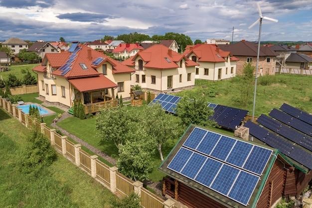Widok z lotu ptaka mieszkalnego prywatnego domu z panelami słonecznymi na dachu i turbiny generatora wiatrowego.