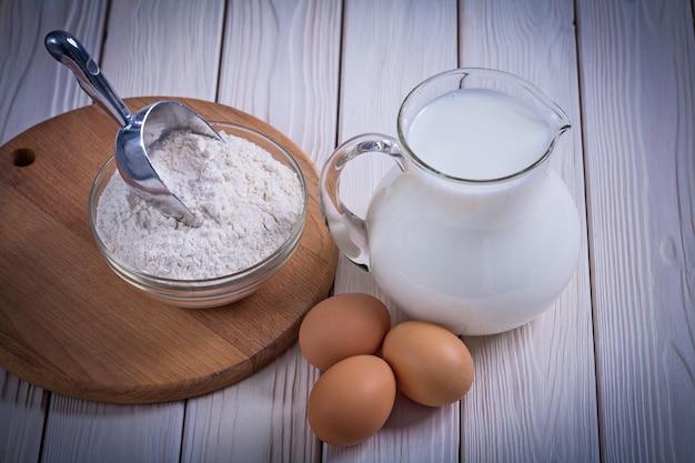 Widok z lotu ptaka mleko jajeczne w dzbanku mąka miska scoopon białe drewno malowane