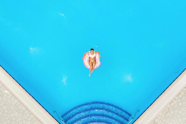 Widok z lotu ptaka młoda piękna dziewczyna relaksuje na nadmuchiwanym pączku w basenie w białym bikini. tło wakacje letnie
