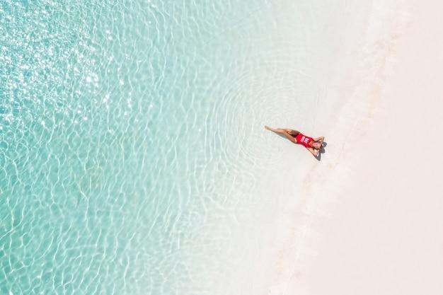 Widok z lotu ptaka młodej kobiety w czerwonym stroju kąpielowym, relaksując się nad brzegiem morza