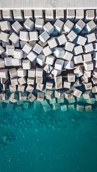 Widok z lotu ptaka młody człowiek na cementowym sześcianie blokuje ochraniać brzeg od fala w porcie malaga, hiszpania.