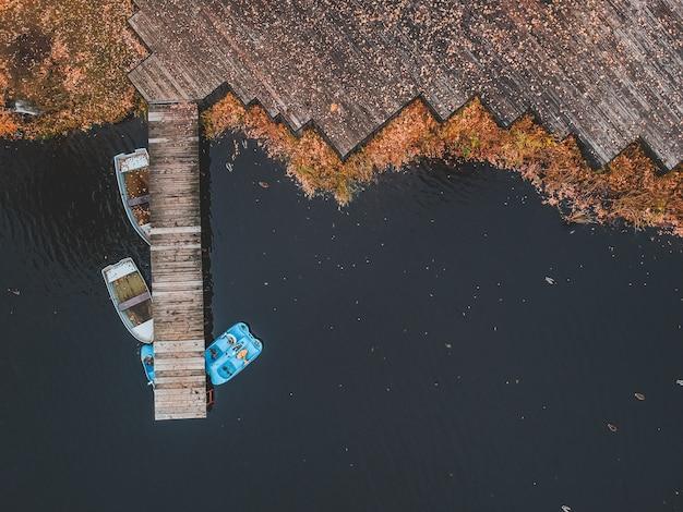 Widok z lotu ptaka molo z drewnianymi łodziami na brzeg malowniczego jeziora, jesień las. sankt petersburg, rosja.