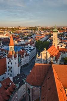 Widok z lotu ptaka monachium - marienplatz i altes rathaus z kościoła św. piotra o zachodzie słońca. monachium, niemcy