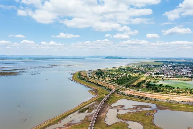 Widok z lotu ptaka mostu kolejowego nad zbiornikiem i społeczności w pobliżu tamy pasak chonlasit w sezonie letnim w lopburi, tajlandia.