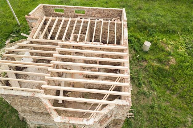Widok z lotu ptaka murowany dom z drewnianą ramą sufitową w budowie.