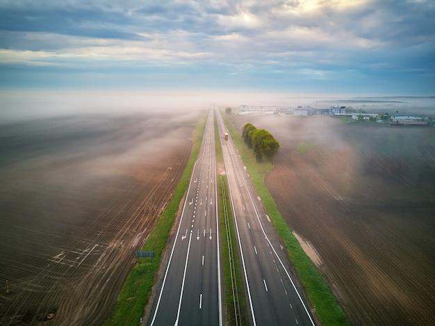 Widok z lotu ptaka na autostradę pokrytą mgłą. wczesny mglisty poranek. droga w polach wiosna lato. autostrada w deszczową pogodę. białoruś, obwód miński