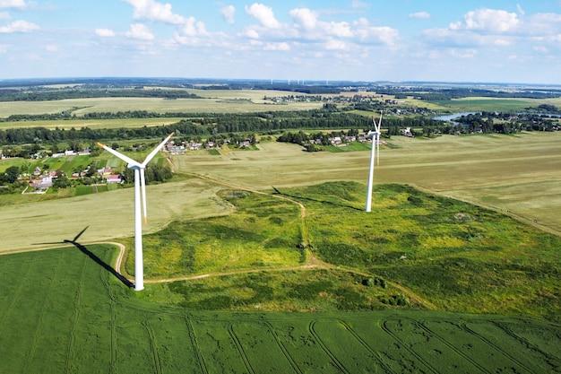 Widok z lotu ptaka na białe turbiny wiatrowe i letnie pola uprawne