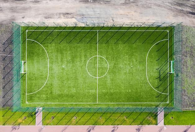 Widok z lotu ptaka na boisko do piłki nożnej z zieloną trawą w parku.