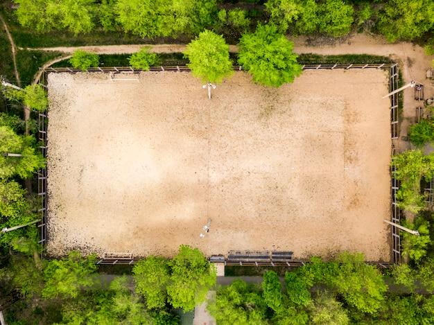 Widok z lotu ptaka na boisko sportowe do siatkówki i piłki nożnej między drzewami