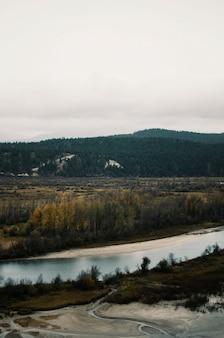 Widok z lotu ptaka na brązową dolinę w pobliżu rzeki pod szarym niebem