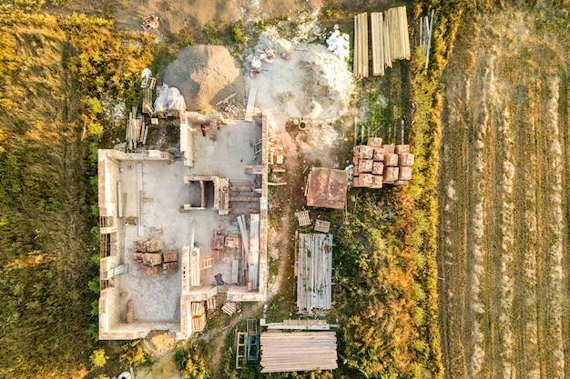 Widok z lotu ptaka na budowany dom z betonowymi fundamentami i ceglanymi ścianami.