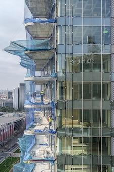 Widok z lotu ptaka na budowę wieżowca, rusztowań, barier, pracowników. 03.01.2020 barcelona, hiszpania