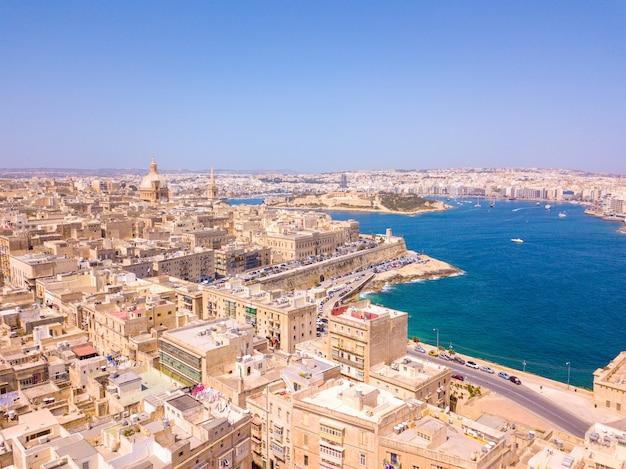 Widok z lotu ptaka na budynki starego miasta w pobliżu wody w valletcie, malta