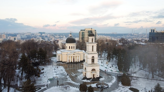 Widok z lotu ptaka na centrum kiszyniowa w zimie. panoramiczny widok na park centralny ze śniegiem, drzewami i wieloma spacerującymi ludźmi, dzwonnicą, katedrą, budynkami w tle.