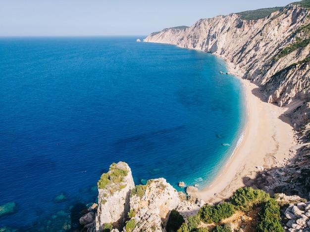 Widok z lotu ptaka na czystą, białą, piaszczystą plażę nad pięknym turkusowym morzem
