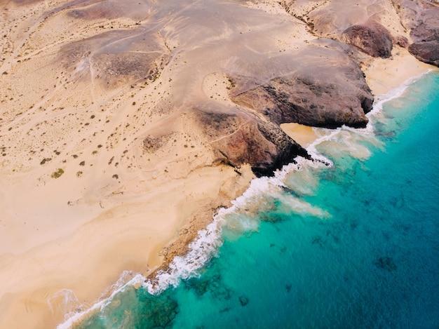 Widok z lotu ptaka na czystą piaszczystą plażę nad oceanem?