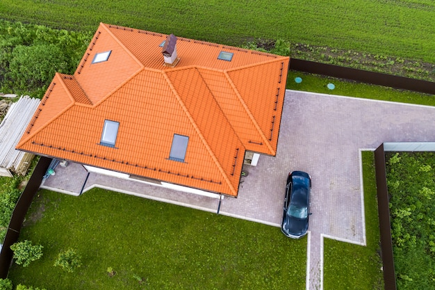 Widok z lotu ptaka na dach domu z gontem, okna na poddaszu i czarny samochód na podwórku