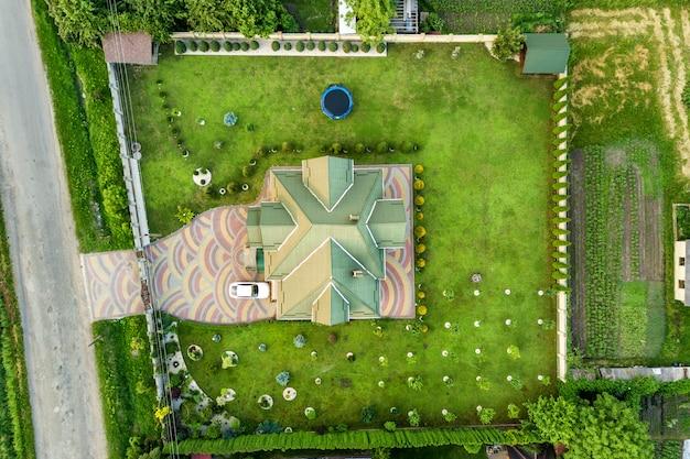 Widok z lotu ptaka na dach gontowy i samochód na utwardzonym podwórku z trawnikiem.
