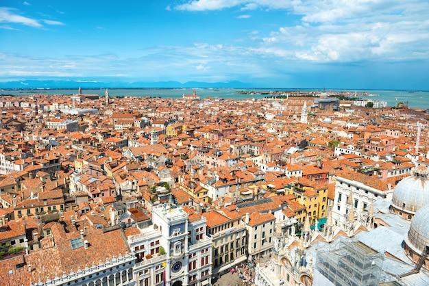 Widok z lotu ptaka na dachy wenecji, domy, morze i ludzi na placu z wieży san marco
