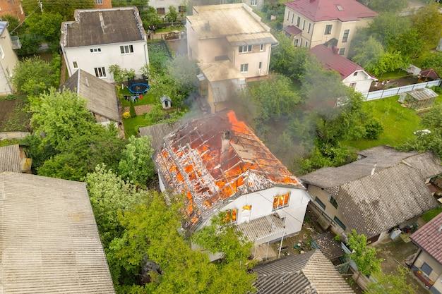 Widok z lotu ptaka na dom w ogniu z pomarańczowymi płomieniami i białym gęstym dymem