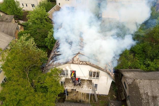 Widok z lotu ptaka na dom w ogniu z pomarańczowymi płomieniami i białym gęstym dymem.