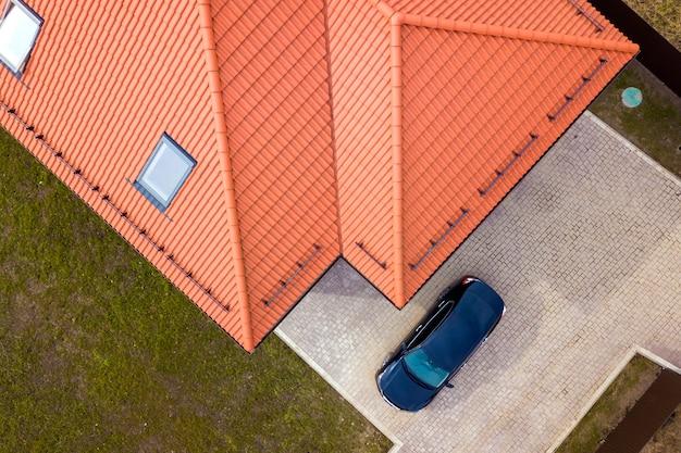 Widok z lotu ptaka na dom z oknami na poddaszu i czarny samochód na utwardzonym podwórku