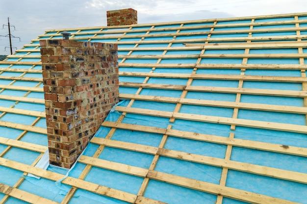 Widok z lotu ptaka na drewnianą konstrukcję dachu murowanego domu w budowie.