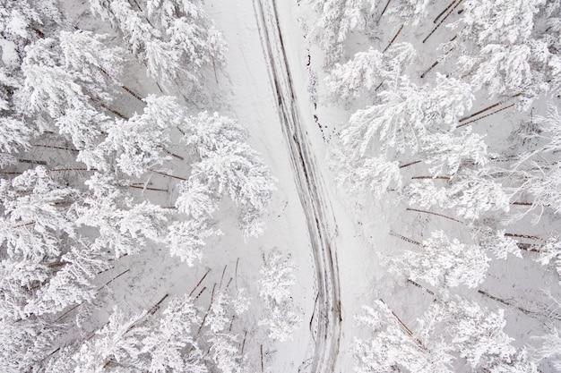 Widok z lotu ptaka na drodze i lesie w czasie zimy. śnieżny las, naturalny zimowy krajobraz.