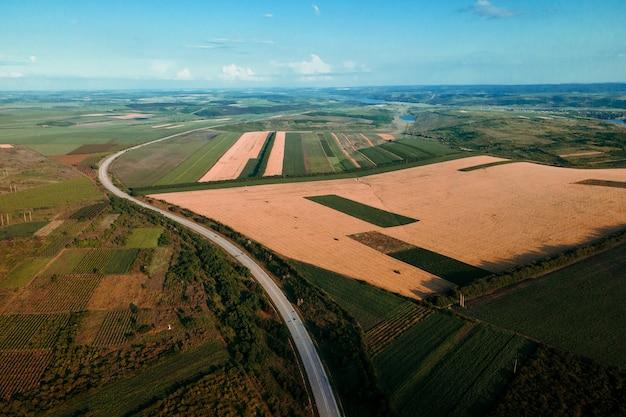 Widok z lotu ptaka na drogę, która przecina pola z różnymi uprawami lot drona nad...