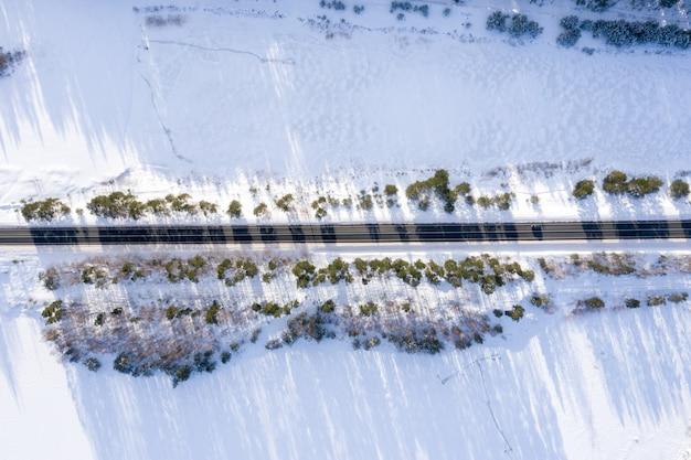 Widok z lotu ptaka na drogę otoczoną drzewami i śniegiem w świetle słonecznym