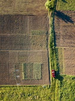 Widok z lotu ptaka na drogę wśród rolniczych pól uprawnych, po których jedzie czerwony samochód. widok z góry strzelają drony. podróż samochodem.