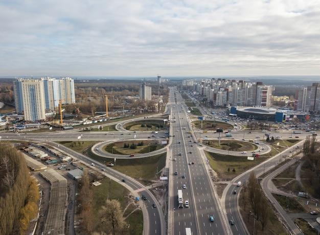 Widok z lotu ptaka na drona na placu w odessie z autostradą w formie czterolistka z przejeżdżającymi samochodami i nowoczesnym miastem na tle zachmurzonego nieba w jesienny dzień. kijów, ukraina