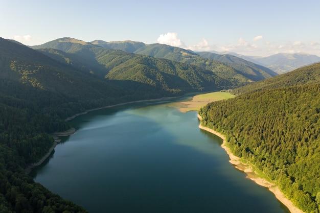 Widok z lotu ptaka na duże jezioro z czystą, błękitną wodą pomiędzy wysokimi wzgórzami pokrytymi gęstym wiecznie zielonym lasem