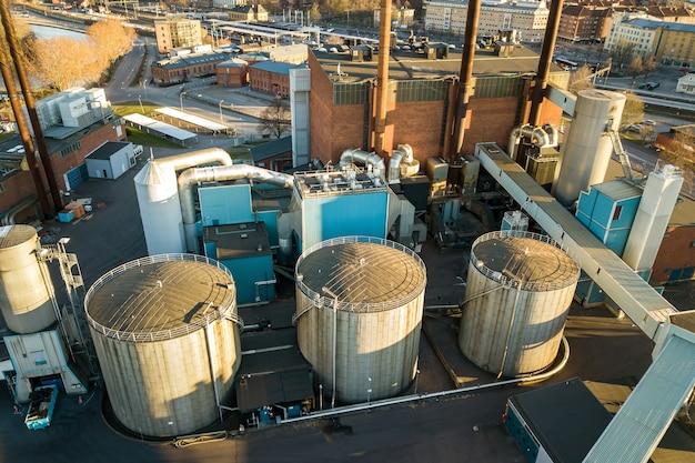 Widok z lotu ptaka na duże zbiorniki paliwa w strefie przemysłowej ropy naftowej i metalowe rury wydechowe fabryki rafinerii ropy naftowej.