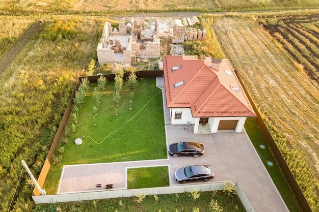 Widok z lotu ptaka na dwa prywatne domy, jeden w budowie z betonowymi fundamentami i ceglanymi ścianami, a drugi wykończony czerwoną dachówką.