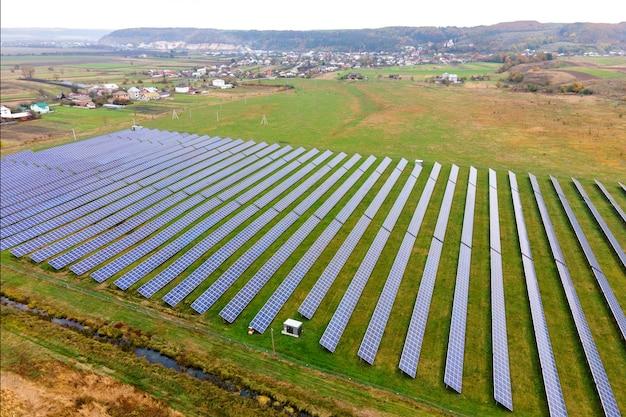 Widok z lotu ptaka na elektrownię słoneczną na zielonym polu. farma elektryczna z panelami do produkcji czystej ekologicznej energii.