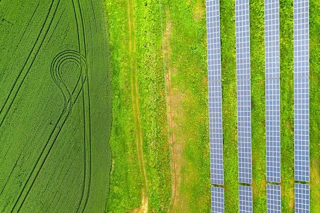 Widok z lotu ptaka na elektrownię słoneczną na zielonym polu. panele elektryczne do produkcji czystej energii ekologicznej.