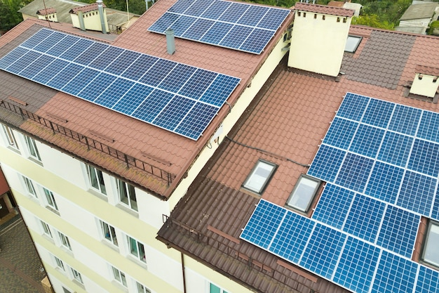 Widok z lotu ptaka na elektrownię słoneczną z niebieskimi panelami fotowoltaicznymi zamontowanymi na dachu budynku mieszkalnego.